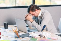 The unsuccessful man sits at the desk and tilted his head in frustration. Inside the office. Stock Photo