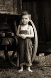 Unsure. Sweet country boy next to a wagon wheel with an antique vintage feel Royalty Free Stock Images