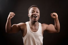 Unsure athlet with brown skin standing with clenched fists. And demonstrating his strength . opened mouth. learn to bodybuild.week boxer royalty free stock photos