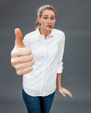 Unsure beautiful girl having dilemmas in showing anxious thumbs up Royalty Free Stock Images