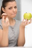 Unsure bewildered girl choosing apple or cake. Royalty Free Stock Image