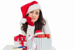 Unsure brunette in santa hat packing gifts Royalty Free Stock Photos