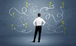 Unsure businessman with question marks Stock Images
