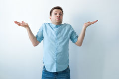 Unsure caucasian man. Young man spreads his hands to the sides Stock Photo