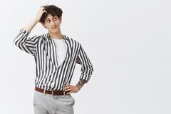 Unsure cute and trendy young jewish guy with curly hair moustache and tattoos scratching head and gazing right with. Clueless unsure expressiong doubting while stock photos