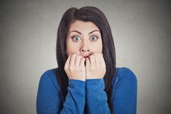 Unsure hesitant nervous woman biting her fingernails craving anxious Royalty Free Stock Photo