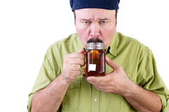 Unsure man tasting cup of herbal tea on white Royalty Free Stock Photos