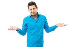 Unsure Man Wearing Blue Shirt While Shrugging His Shoulders. Portrait of unsure man wearing blue shirt while shrugging his shoulders over white background stock images