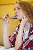 Unsure student holding pen during class. At the university stock photos