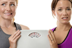Unsure what to do. Two fitness women holding scales unsure and afraid to weight themselves royalty free stock image