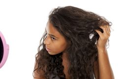 Unsure woman. Unsure young dark skinned woman in front of mirror stock images
