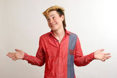 Unsured guy with golden hairstyle in the red shirt. Dilute hands over white background Stock Photo