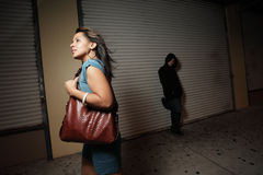 Unsuspecting woman. Woman walking on the streets unsuspecting a stalker lurking in the shadows royalty free stock images