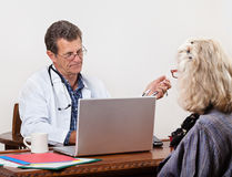 Unsympathetic Doctor Listens to Patient Royalty Free Stock Images