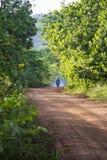 Untarred wiejska droga z dymiącym motocyklem Obrazy Royalty Free