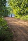 Untarred wiejska droga z dymiącym motocyklem Fotografia Royalty Free