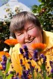 Untaugliche Frau, die auf Gras und Geruch auf Blumen liegt Stockbild