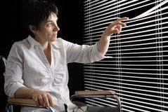 Untaugliche Frau im Rollstuhl, der Abflussrinnevorhänge schaut Stockbild