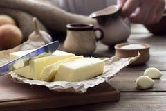 Unte con mantequilla con un cuchillo y una taza con leche Imagen de archivo