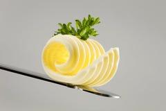 Unte con mantequilla el enrollamiento en un cuchillo Imagenes de archivo