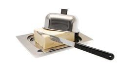 Unte con mantequilla en el plato de mantequilla de plata con el cuchillo Fotografía de archivo libre de regalías