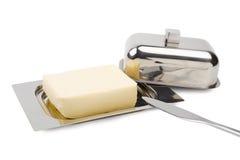 Unte con mantequilla en el plato de mantequilla de plata, cuchillo, aislado Imágenes de archivo libres de regalías