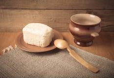 Unte con mantequilla en la placa, el pote de arcilla y la cuchara en la servilleta de lino Stil rústico Foto de archivo libre de regalías