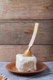 Unte con mantequilla en la placa, el pote de arcilla y la cuchara en la servilleta de lino Stil rústico Fotografía de archivo