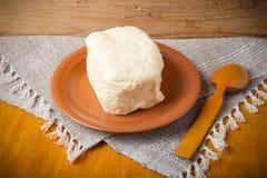 Unte con mantequilla en la placa, el pote de arcilla y la cuchara en la servilleta de lino Stil rústico Fotos de archivo
