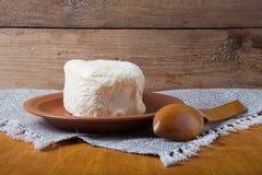 Unte con mantequilla en la placa, el pote de arcilla y la cuchara en la servilleta de lino Stil rústico Imágenes de archivo libres de regalías