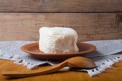 Unte con mantequilla en la placa, el pote de arcilla y la cuchara en la servilleta de lino Stil rústico Foto de archivo