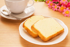 Unte con mantequilla la torta cortada en la taza de la placa y de café, imagen filtrada Imagen de archivo