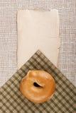 Unte con mantequilla un bollo redondo - panecillo Foto de archivo