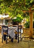 Unter Baumcafétabellen auf dem Dorfplatz, Vourliotes, Samos, Stockbild
