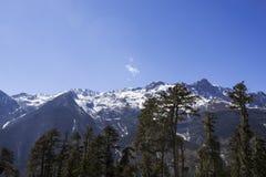 Unter dem blauen Himmel und dem Schnee bedeckte Berge mit einer Kappe Lizenzfreie Stockfotos