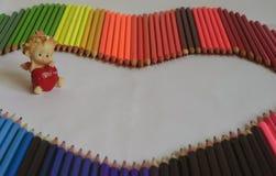 Unter den farbigen Bleistiften auf einer weißen Hintergrundengelszahl, die ich liebe dich ein rotes Herz in den Händen und im Wör Stockbilder