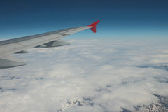 Unter flachen bewölkten und schneebedeckten Bergen des Flügels lizenzfreie stockfotografie