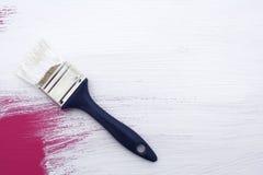 Unter Verwendung über Rosa mit weißer Emulsion zu malen des Malerpinsels, lizenzfreie stockbilder