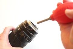 Unter Verwendung der Luftpumpe zum Säubern von Kameraobjektiv Lizenzfreie Stockfotografie