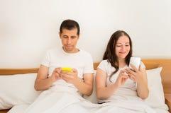 Unter Verwendung der Smartphones im Bett Stockbild
