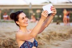 Unter Verwendung der Tablette auf Strand stockfotos