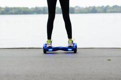 Unter Verwendung des elektrischen intelligenten Rollers selbstabgleichendes Hoverboard Stockfotos