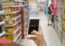 Unter Verwendung des Handys im Markt stockfoto