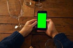 Unter Verwendung des Handys im Restaurant Stockbilder