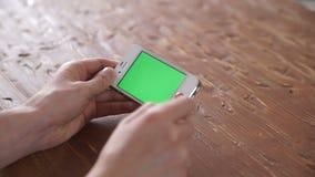 Unter Verwendung des intelligenten Telefons auf den verschiedenen Handzeichen der hölzernen Tabelle, vertikal stock video footage