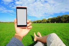 Unter Verwendung des intelligenten Telefons mit Natur Stockfotos