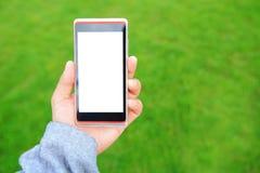 Unter Verwendung des intelligenten Telefons mit Natur Stockbild