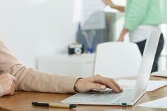 Unter Verwendung des Laptops bei der Arbeit Lizenzfreie Stockfotos