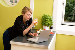 Unter Verwendung des Laptops in der Küche Stockbilder