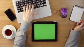 Unter Verwendung des Laptops und des Tablet-PCs mit einem grünen Schirm stock video footage